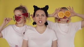 Drie meisjes die pret op gele achtergrond hebben Kauwgom, spelend met suikergoed en fruit stock videobeelden