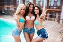 Drie meisjes die zich dichtbij zwembad bevinden en tonend vredesteken Stock Foto's