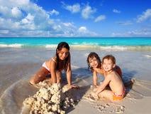 Drie meisjes gemengd het behoren tot een bepaald ras het spelen strand Stock Afbeeldingen