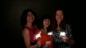 Drie meisjes holdingsparkling stokken in hun handen stock footage
