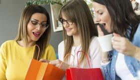 Drie meisjes kijken in de zak wat zij het winkelen inkochten royalty-vrije stock afbeelding