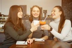 Drie meisjes komen in koffie samen Drinkende dranken en het spreken van elkaar stock foto