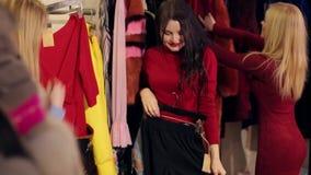 Drie meisjes kopen nieuwe kleren in een manieropslag in een groot winkelcentrum stock videobeelden