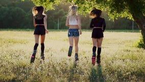 Drie meisjes in laarzen met de lentes die het de zomerpark die bij zonsondergang doornemen sporten doen stock footage