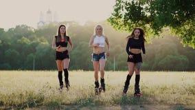 Drie meisjes in laarzen met de lentes die het de zomerpark die bij zonsondergang doornemen sporten doen stock videobeelden