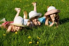 Drie meisjes liggen in het gras Royalty-vrije Stock Foto