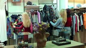 Drie meisjes lopen in een kledingsopslag, bekijken zij kleren en proberen het stock videobeelden