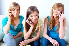 Drie meisjes met mobiele telefoons Stock Afbeeldingen