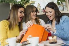 Drie meisjes na het winkelen genieten van koffie en koekjes stock foto