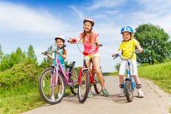 Drie meisjes op bedekken weg met fietsen Stock Afbeeldingen