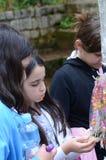 Drie meisjes op de leeftijd van zeven of acht het kopen suikergoed in een pretpark Royalty-vrije Stock Fotografie