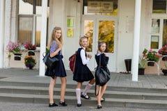 Drie meisjes in school eenvormig met rugzakkentribune op de stappen stock foto