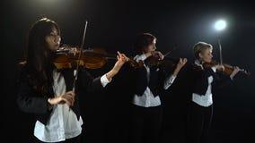 Drie meisjes in spel de violen in een samenstelling in een ruimte Zwarte achtergrond stock footage