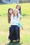 Drie meisjes troffen voor het reizen met koffer voorbereidingen Stock Fotografie