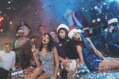 Drie meisjes zitten op de vloer en zijn bored Zij zijn zeer vermoeid na een daverende partij voor het nieuwe jaar Stock Foto's