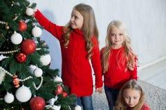 Drie meisjesblonden verfraaien Kerstboom nieuw jaar royalty-vrije stock foto's