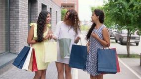 Drie meisjesmeisjes bespreken het winkelen na het winkelen Langzame Motie stock videobeelden