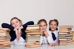 Drie meisjesschoolmeisjes bij een bureau met boeken op de les op school stock fotografie