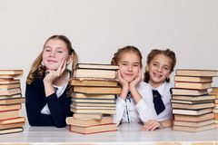 Drie meisjesschoolmeisjes bij een bureau met boeken op de les op school royalty-vrije stock foto's