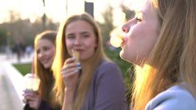 Drie meisjesvrienden die pret bij broadway gelijk maken hebben Etend roomijs, drinkend ijs verse milkshake en het kauwen bel stock videobeelden