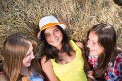 Drie meisjesvrienden die pret op hooistapel hebben Stock Afbeelding