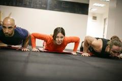 Drie mensen bij de gymnastiek Royalty-vrije Stock Fotografie