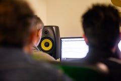 Drie mensen die een lied in een productiestudio uitgeven stock afbeelding