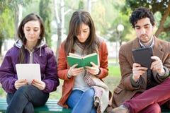 Drie Mensen die in een Park lezen stock afbeelding