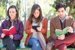Drie Mensen die in een Park lezen stock foto