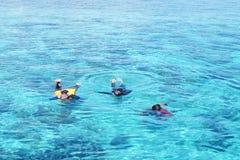 Drie mensen die in het overzeese turkooise duidelijke water snorkelen stock fotografie