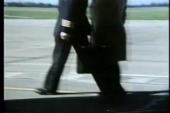 Drie mensen die op tarmac aan propellervliegtuig lopen stock videobeelden