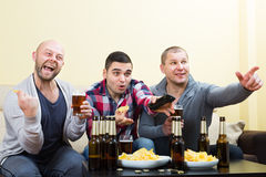Drie mensen die op voetbal met bier letten binnen Stock Foto
