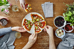 Drie mensen die organische heerlijke pizza delen bij dinerpartij royalty-vrije stock fotografie