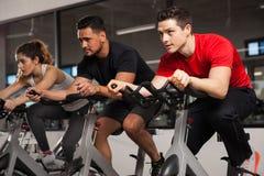 Drie mensen doen cardio op een fiets Stock Afbeeldingen