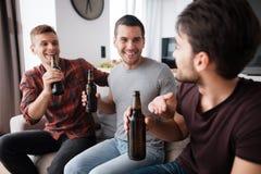 Drie mensen drinken bier van donkere flessen Zij zitten op de laag en het glimlachen Stock Afbeeldingen