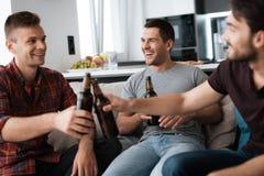 Drie mensen drinken bier van donkere flessen Zij zitten op de laag en het glimlachen Royalty-vrije Stock Afbeeldingen