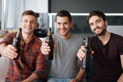 Drie mensen drinken bier van donkere flessen Zij zitten op de laag en het glimlachen Stock Foto's