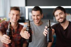 Drie mensen drinken bier van donkere flessen Zij zitten op de laag en het glimlachen Royalty-vrije Stock Foto's