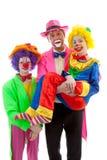 Drie mensen kleedden zich omhoog als kleurrijke grappige clowns Stock Afbeeldingen