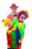 Drie mensen kleedden zich omhoog als kleurrijke grappige clowns Stock Foto