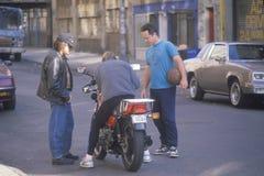 Drie mensen met een motorfiets royalty-vrije stock foto