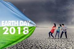 Drie mensen met tekst van Aarde Dag 2018 Royalty-vrije Stock Afbeelding