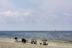 Drie mensen op het strand op de achtergrond van het overzees stock afbeelding