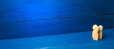 Drie mensen verenigen zich en spreken Drie houten cijfers van mensen leiden een gesprek op een blauwe achtergrond Mededeling stock foto