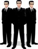Drie mensen in zwarte kostuums Stock Foto's