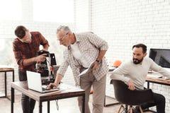 Drie mensenopstelling een zelf-gemaakte 3d printer om de vorm te drukken Zij controleren het 3d model op laptop Royalty-vrije Stock Fotografie