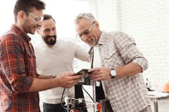 Drie mensenopstelling een zelf-gemaakte 3d printer om de vorm te drukken Zij controleren het 3d model van de tablet Royalty-vrije Stock Fotografie