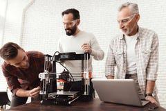 Drie mensenopstelling een zelf-gemaakte 3d printer om het werkstuk te drukken Een bejaarde met laptop let op zijn collega's Stock Foto