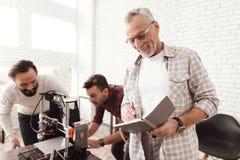 Drie mensenopstelling een zelf-gemaakte 3d printer om het werkstuk te drukken Een bejaarde met een notitieboekje die op zijn coll Stock Foto