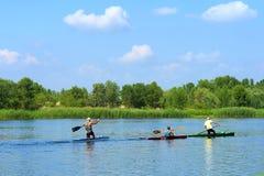 Drie mensenrij in boten Royalty-vrije Stock Afbeelding